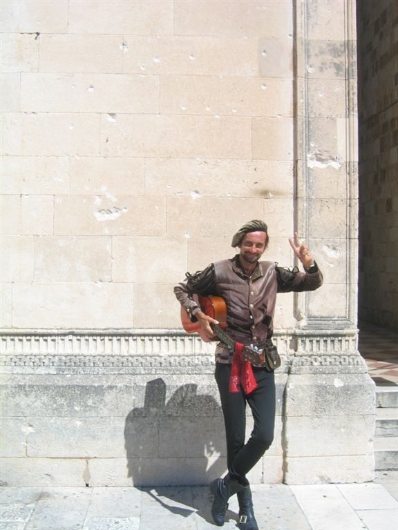 Street Performer in Dubrovnik.  Notice the Bullet Holes and Shelling Marks in the wall behind him!!!  They are reminders of the war in Dubrovnik only a dozen years ago!!!